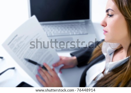 Business woman in an office with laptop - stock photo