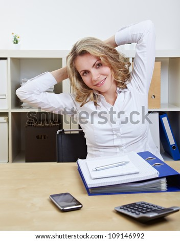Business woman in office at her desk stretching her back - stock photo