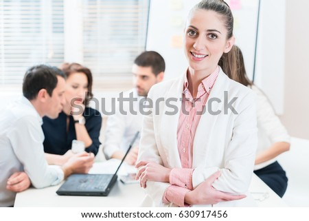 Business woman in office, people working in background