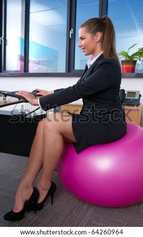 business woman in office working on computer while sitting on pilates ball