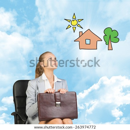 Business woman in skirt, blouse and jacket, sitting on chair and holding briefcase imagines house with tree. Against background of blue sky and clouds - stock photo