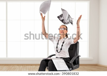 Business woman in the office next to a window scatter documents