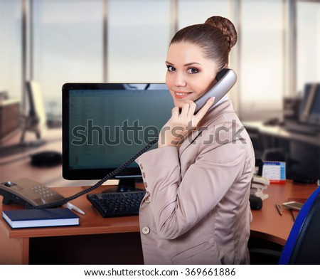business woman in the office talking on the phone.Woman On Phone In Busy Modern Office