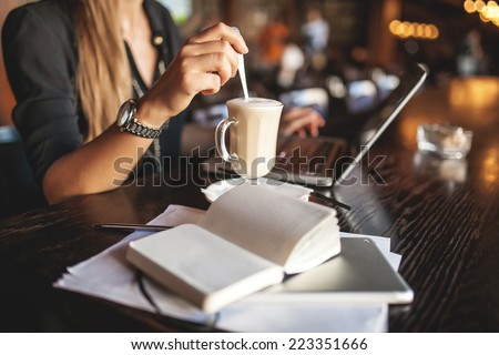 Business woman indoor with coffee and laptop taking notes - stock photo