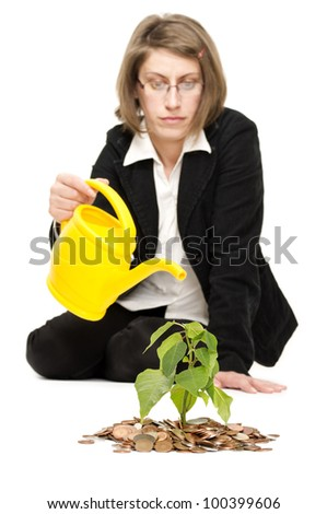 Business woman irrigating a plant with coins. Financial investment metaphor. Isolated on white. - stock photo