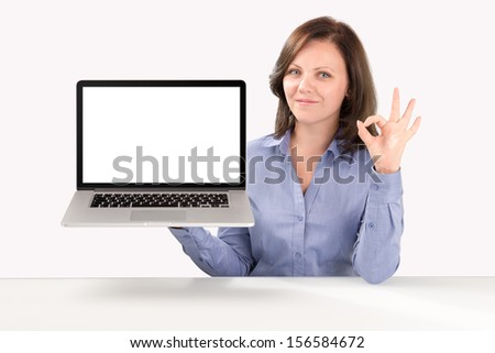Business woman is holding a laptop in one hand and by other hand showing ok gesture, business concept - stock photo
