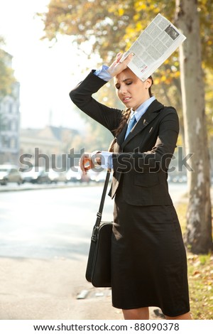 business woman is late for work or a meeting, looking in watch - stock photo