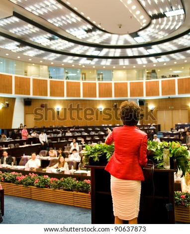 Business woman is making a speech in front of a big audience at a conference hall. - stock photo