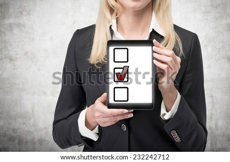 Business woman is presenting a tablet screen with boxes for ticking.