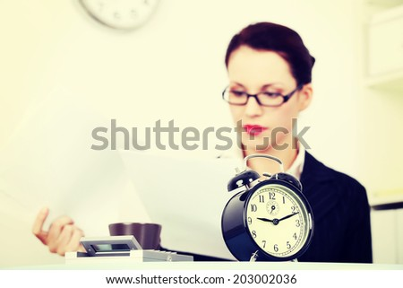 Business woman is working in office and holding some documents. Clock in front, deadline concept. - stock photo