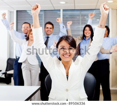 Business woman leading a successful group with arms up - stock photo