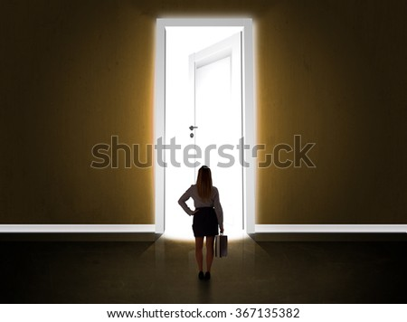 Business woman looking at big bright opened door concept - stock photo