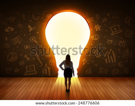 Business woman looking at bright light bulb in the wall concept - stock photo