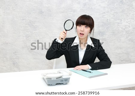 business woman looking into a magnifying glass - stock photo