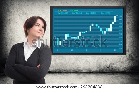 business woman looking up and financial graph on screen