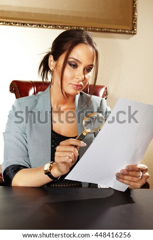 business woman looks on one document by magnifying glass - stock photo