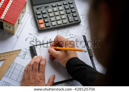 Business woman makes calculations, drawings, diagram, writes the formula on table with blueprints, toy house and calculator.