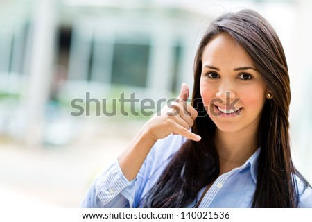 Business woman making a call me sign and smiling - stock photo