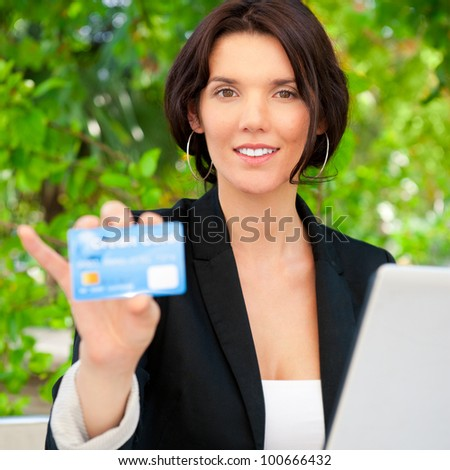 Business woman making payments online using laptop and credit card sitting outdoor at cafe with wireless internet