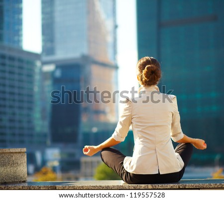 Business woman meditating and making yoga outdoor over building background