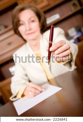 business woman offering her pen to seal the deal - stock photo