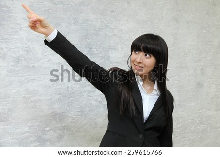 Business woman pointing at something with smile - stock photo