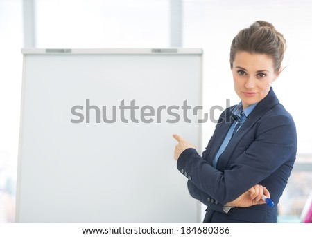 Business woman pointing on flipchart - stock photo