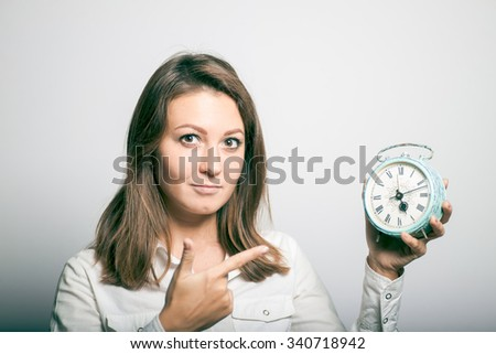 Business woman points at her watch. office manager. studio photo on a gray background