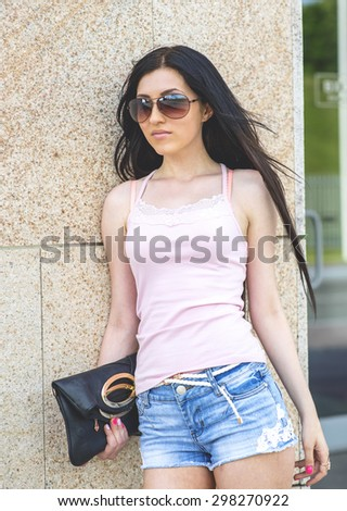 Business woman posing in a business building with a bag in his hand and wearing glasses, a beautiful woman, fashion style urban portrait, bright sunny summer day in front of the school , sexy - stock photo