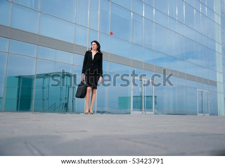 Business woman posing with a laptop's bag in a front of modern office building