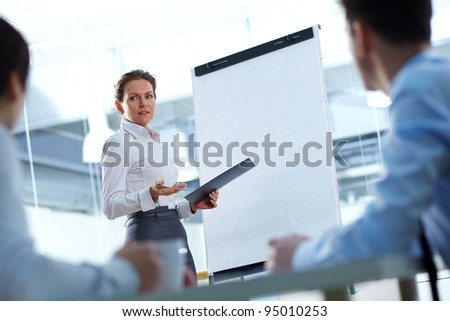 Business woman presenting a new project to her partners - stock photo
