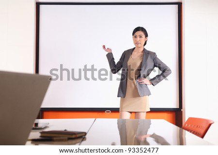 business woman presenting on blank room - stock photo