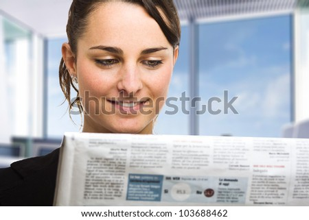 Business woman reading a newspaper - stock photo
