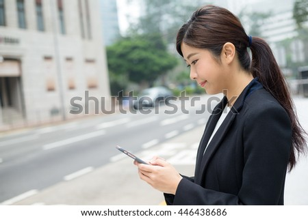 Business woman reading on her cellphone