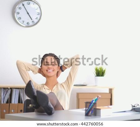 Business woman relaxing with hands behind her head and sitting on an office chair - stock photo
