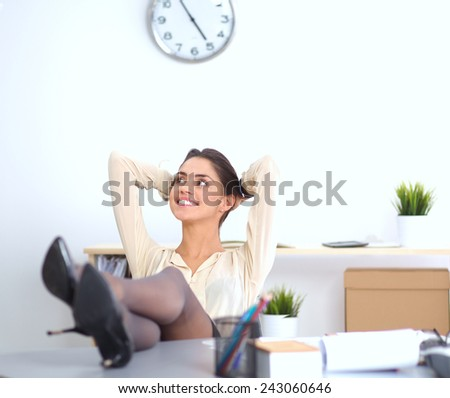 Business woman  relaxing with her hands behind her head and sitting on a chair