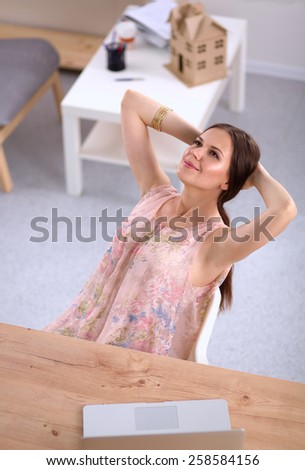 Business woman relaxing with her hands behind her head and sitting on a chair. - stock photo