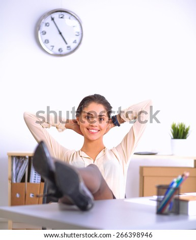 Business woman  relaxing with her hands behind her head and sitting on a chair - stock photo