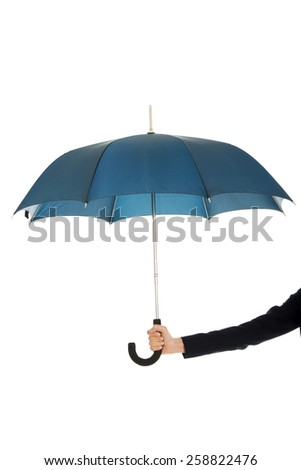 Business woman's hand is holding blue umbrella. - stock photo