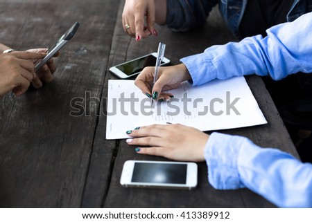 Business woman's hand with pen completing application form on wooden table