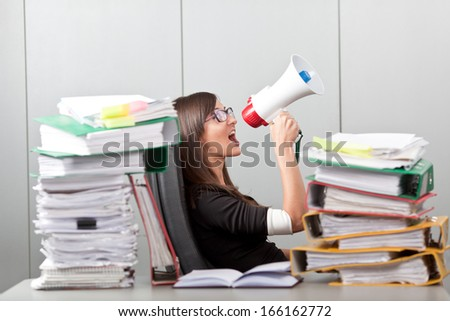 Business woman screaming with a megaphone Business Woman in the office overworked - stock photo