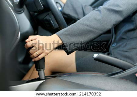 Business woman shifting the gear stick for driving a car
