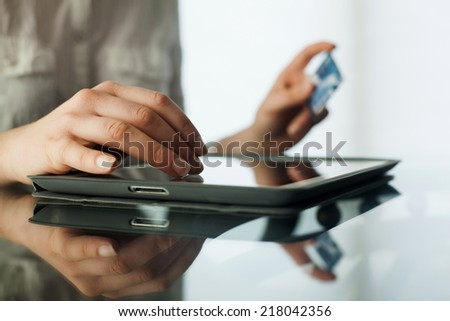 Business woman shopping using tablet pc and credit card - stock photo