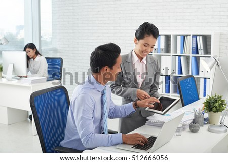Business woman showing application on tablet computer to her colleague