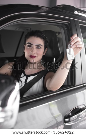 Business woman showing keys sitting in the SUV car and looking at camera