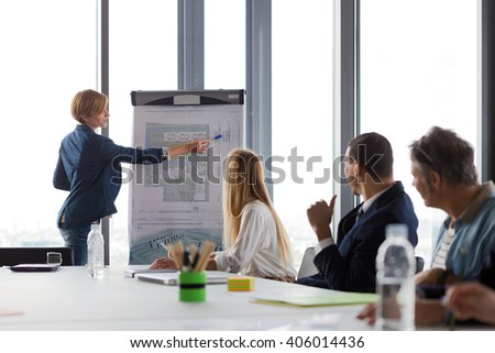 Business woman showing project details  on ground-plan at meeting in modern office. - stock photo