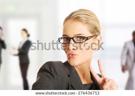 Business woman showing victory or peace sign. - stock photo