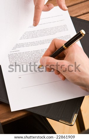 Business woman signing a contract with a fountain pen - stock photo