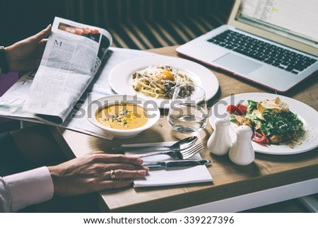 Business woman sits in cafe and reads the newspaper. Three plates with lunch dishes on wooden table. Caesar salad, pumpkin soup and pasta carbonara. Toned image - stock photo