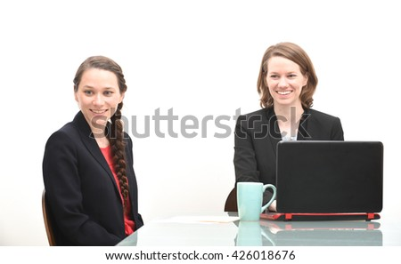 Business woman sitting at conference room table smiling while listening - stock photo